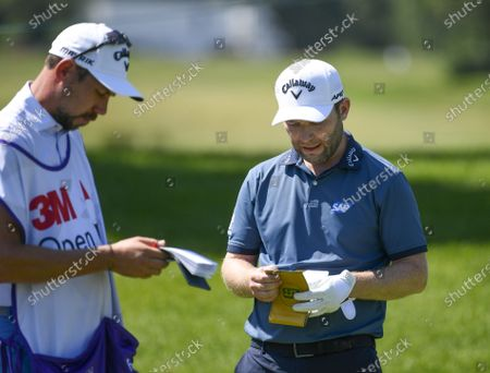 Stock Photo of Branden Grace (R) of George, South Africa, checks his notes before teeing off on the eighth hole during the second round of the 3M Open golf tournament at the TPC Twin Cities course in Blaine, Minnesota, USA, 24 July, 2020.