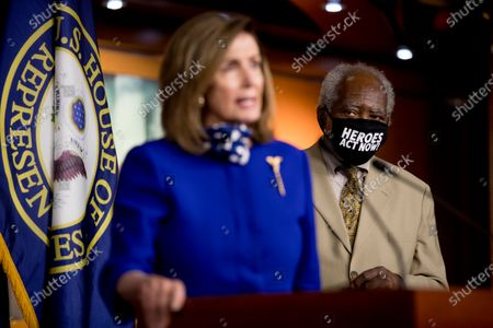 """Rep. Danny Davis, D-Ill., right, wears a mask that reads """"Heroes Act Now"""" as House Speaker Nancy Pelosi of Calif., left, speaks during a news conference on Capitol Hill in Washington, on the extension of federal unemployment benefits"""