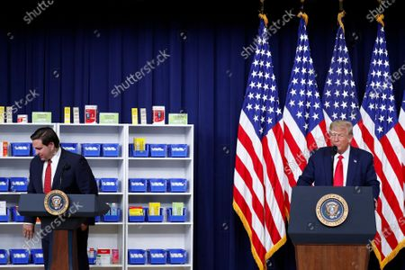 Stock Image of Governor Ron DeSantis (Republican of Florida), left, departs after speaking during an executive order signing ceremony on lowering drug prices in the Eisenhower Executive Office Building in Washington, D.C., U.S.,. Looking on from right is United States President Donald J. Trump. Lowering prescription drug prices is a top priority of Trump including a policy to tie Medicare payments to foreign countries' drug prices.