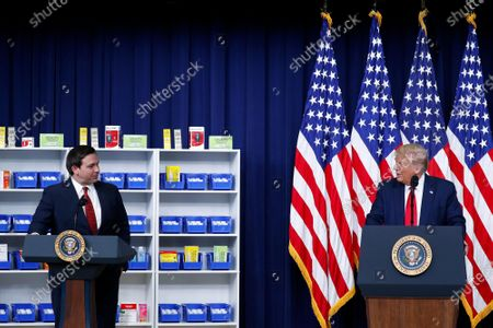 United States President Donald J. Trump, right, speaks to Governor Ron DeSantis (Republican of Florida), during an executive order signing ceremony on lowering drug prices in the Eisenhower Executive Office Building in Washington, D.C., U.S.,. Lowering prescription drug prices is a top priority of Trump including a policy to tie Medicare payments to foreign countries' drug prices.