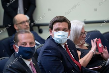 United States Secretary of Health and Human Services (HHS) Alex Azar and Governor Ron DeSantis (Republican of Florida), center, wear protective face masks while attending an executive order signing ceremony on lowering drug prices in the Eisenhower Executive Office Building in Washington, D.C., U.S.,. Lowering prescription drug prices is a top priority of Trump including a policy to tie Medicare payments to foreign countries' drug prices.