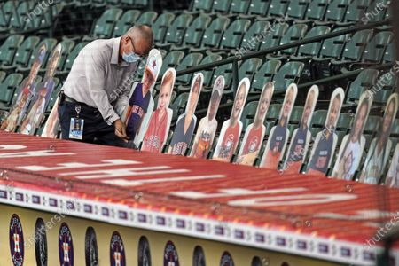 Houston Astros staff member Thomas Bell puts places cutouts of team family members in the stands before a baseball game against the Seattle Mariners, in Houston