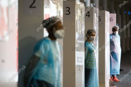 Health employees wearing face mask at a covid testing center at Roissy-Charles de Gaulle airport, north of during a visit as sanitary measures have been deployed for departing and arriving passengers in order to curb the spread of the COVID-19 pandemic, caused by the novel coronavirus. Europe hit more than three million coronavirus cases on July 23, while spiking infection numbers worldwide led authorities to reimpose restrictions on citizens.