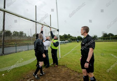 Stock Image of Thurles Sarsfields vs Kilruane MacDonaghs. Referee Michael Kennedy looks on as the nets are repaired before the start of the game