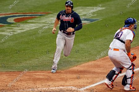 Atlanta Braves' Adam Duvall, left, scores a run behind New York Mets catcher Wilson Ramos during the tenth inning of a baseball game, in New York