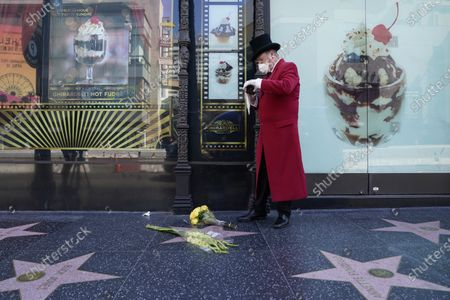 Gregg Donovan, unofficial ambassador of Hollywood, takes a photo after laying flowers on legendary television personality Regis Philbin's star on the Hollywood Walk of Fame, in the Hollywood area of Los Angeles. Philbin has died, at age 88
