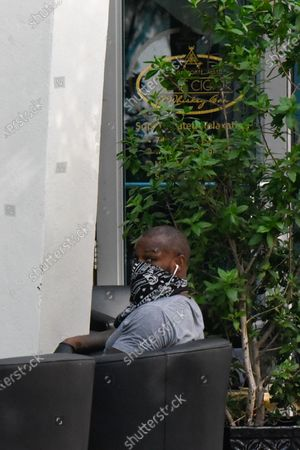American model and actor Tyson Beckford wearing a bandana as a face covering and gloves is sighted in downtown Miami
