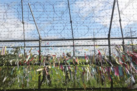 "South Korean army soldiers wearing face masks to help protect against the spread of the new coronavirus pass by a wire fence decorated with ribbons written with messages wishing for the reunification of the two Koreas at the Imjingak Pavilion in Paju, near the border with North Korea, . North Korean leader Kim Jong Un placed the city of Kaesong near the border with South Korea under total lockdown after a person was found with suspected COVID-19 symptoms, saying he believes ""the vicious virus"" may have entered the country, state media reported Sunday"