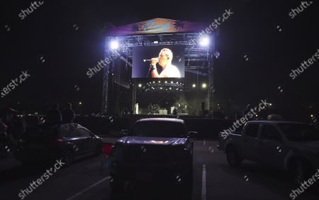 Stock Image of Lead singer Stephan Jenkins is shown on a video screen above the stage as audience members watch Third Eye Blind's performance at Concerts in your Car at the Ventura County Fairgrounds, in Ventura, Calif