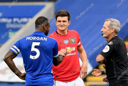 Manchester United's Harry Maguire, centre, shakes hands with Leicester's Wes Morgan, left, before the English Premier League soccer match between Leicester City and Manchester United at the King Power Stadium, in Leicester, England
