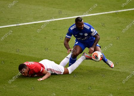 Leicester's Wes Morgan, right, duels for the ball with Manchester United's Anthony Martial during the English Premier League soccer match between Leicester City and Manchester United at the King Power Stadium, in Leicester, England
