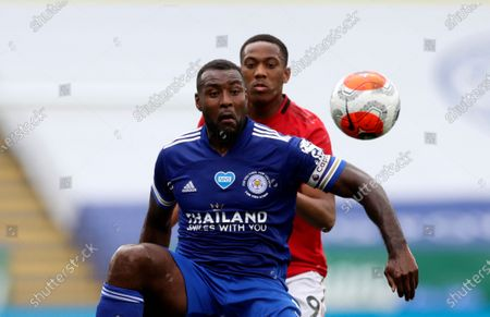 Leicester's Wes Morgan, front, duels for the ball with Manchester United's Anthony Martial during the English Premier League soccer match between Leicester City and Manchester United at the King Power Stadium, in Leicester, England