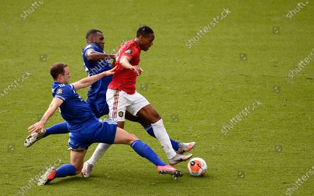 Manchester United's Anthony Martial, centre, duels for the ball with Leicester's Jonny Evans, front, and Leicester's Wes Morgan during the English Premier League soccer match between Leicester City and Manchester United at the King Power Stadium, in Leicester, England