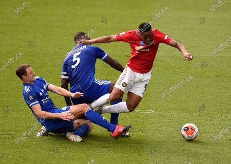 Manchester United's Anthony Martial, right, duels for the ball with Leicester's Jonny Evans, left, and Leicester's Wes Morgan during the English Premier League soccer match between Leicester City and Manchester United at the King Power Stadium, in Leicester, England