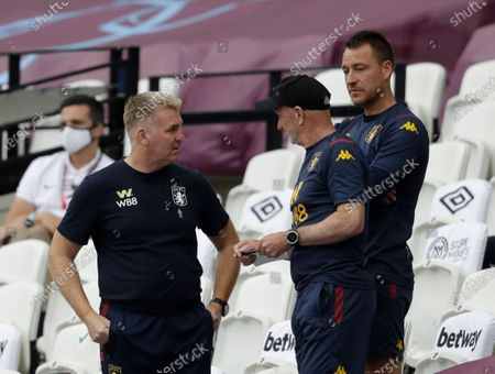 Aston Villa's head coach Dean Smith, left speaks to members if his coaching staff Richard O'Kelly, center and John Terry, during the English Premier League soccer match between West Ham United and Aston Villa at the London Stadium in London
