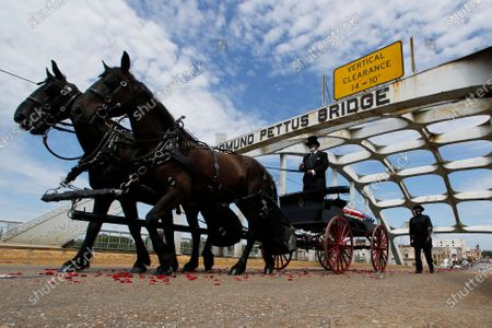 The casket of Rep. John Lewis moves over the Edmund Pettus Bridge by horse drawn carriage during a memorial service for Lewis, in Selma, Ala. Lewis, who carried the struggle against racial discrimination from Southern battlegrounds of the 1960s to the halls of Congress, died Friday, July 17, 2020