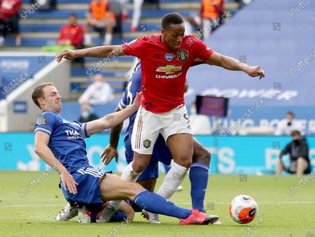 Manchester United's French striker Anthony Martial (R) is brought down by challenges from Leicester City's Northern Irish defender Jonny Evans (L) and Leicester City's English-born Jamaican defender Wes Morgan (C) to concede a penalty leading to the opening goal for Manchester United during the English Premier League football match between Leicester City and Manchester United at King Power Stadium in Leicester, Britain, 26 July 2020.