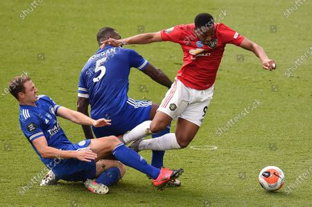 Manchester United's Anthony Martial (R) duels for the ball with Leicester's Jonny Evans (L) and Wes Morgan (C) during the English Premier League soccer match between Leicester City and Manchester United at the King Power Stadium, in Leicester, Britain, 26 July 2020.