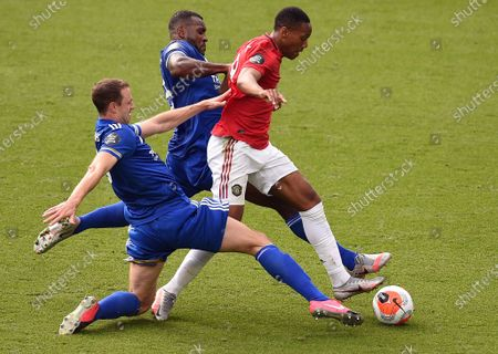 Manchester United's French striker Anthony Martial (R) goes down under challenges from Leicester City's English-born Jamaican defender Wes Morgan (C) and Leicester City's Northern Irish defender Jonny Evans (L) to win a penalty during the English Premier League football match between Leicester City and Manchester United at King Power Stadium in Leicester, Britain, 26 July 2020.
