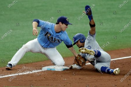 Stock Photo of Tampa Bay Rays third baseman Joey Wendle, left, is late with the tag as Toronto Blue Jays' Santiago Espinal steals third base during the 10th inning of a baseball game, in St. Petersburg, Fla