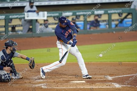 Houston Astros' Taylor Jones grounds into a double play as Seattle Mariners catcher Joe Hudson reaches for the pitch during the second inning of a baseball game, in Houston