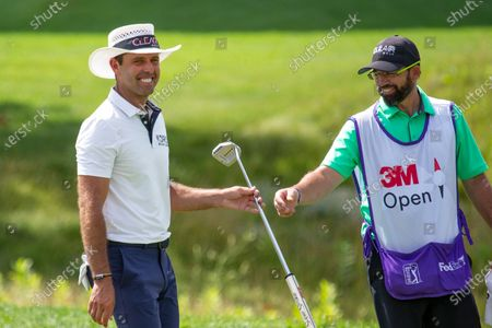 Charl Schwartzel and his caddie smile after Schwartzel birdied the 13th hole during the final round of the 3M Open golf tournament in Blaine, Minn