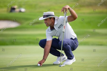 Charl Schwartzel lines a putt up on the 18th hole during the final round of the 3M Open golf tournament in Blaine, Minn