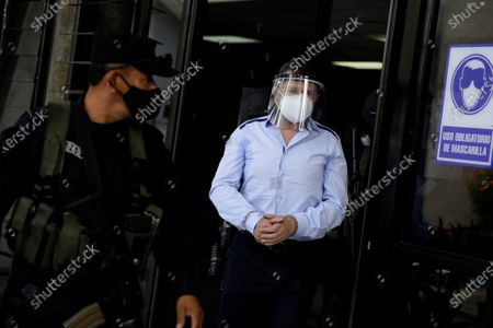 Salvadoran former Minister of Defense and Security David Munguia Payes (R) is guarded by police at the 'Isidro Menendez' judicial center in San Salvador, El Salvador, 26 July 2020. The former Minister of Defense and Security David Munguia Payes and former President Mauricio Funes (2009-2014) were formally accused on 26 July for allegedly favoring the main gangs in the country within the framework of a pact that took place between 2012 and 2014 to lower the homicide figure.