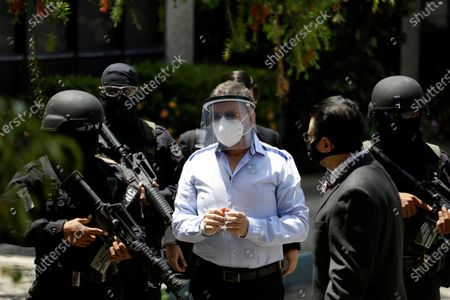 Salvadoran former Minister of Defense and Security David Munguia Payes (C) is guarded by police at the 'Isidro Menendez' judicial center in San Salvador, El Salvador, 26 July 2020. The former Minister of Defense and Security David Munguia Payes and former President Mauricio Funes (2009-2014) were formally accused on 26 July for allegedly favoring the main gangs in the country within the framework of a pact that took place between 2012 and 2014 to lower the homicide figure.