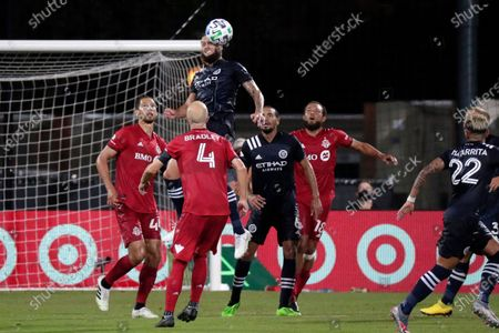 New York City FC defender Maxime Chanot goes up for a header over Alexander Callens (6) and Toronto FC defender Omar Gonzalez, midfielder Michael Bradley (4) and midfielder Nick DeLeon during the first half of an MLS soccer match, in Kissimmee, Fla