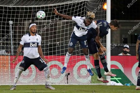 Sporting Kansas City midfielder Graham Smith (16) tries to head into the goal on a corner kick against Vancouver Whitecaps midfielder Leonard Owusu (17) and defender Derek Cornelius (13) defend during the first half of an MLS soccer match, in Kissimmee, Fla