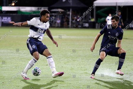 Vancouver Whitecaps forward Theo Bair, left, looks for a shot against Sporting Kansas City midfielder Graham Smith during the second half of an MLS soccer match, in Kissimmee, Fla