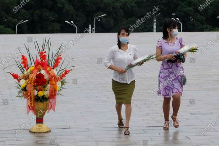 """People visit the statues of former North Korean leaders Kim Il Sung and Kim Jong Il to lay flowers on the occasion of the 67th anniversary of the end of the Korean War, which the country celebrates as the day of """"victory in the fatherland liberation war"""" in Pyongyang"""