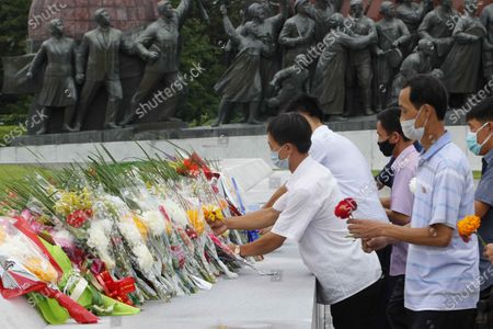 """People lay flowers the statues of former North Korean leaders Kim Il Sung and Kim Jong Il on the occasion of the 67th anniversary of the end of the Korean War, which the country celebrates as the day of """"victory in the fatherland liberation war"""" in Pyongyang"""