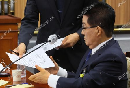 Stock Photo of National Intelligence Service (NIS) chief nominee Park Jie-won looks at a copy of a secret inter-Korean agreement carrying his signature during his confirmation hearing at the intelligence committee of the National Assembly in Seoul, South Korea, 27 July 2020. Park denied that it was his signature, saying, 'I don't remember (signing the agreement).' He visited the North as a presidential envoy of then-President Kim Dae-jung in April 2000 prior to the inter-Korean summit held in Pyongyang on June 15 that year. According to the disclosed accord, signed on April 8, Park agreed to secretly provide US dollars 500 million to the North based on a humanitarian spirit. Rep. Joo Ho-young, floor leader of the main opposition United Future Party, disclosed the accord.