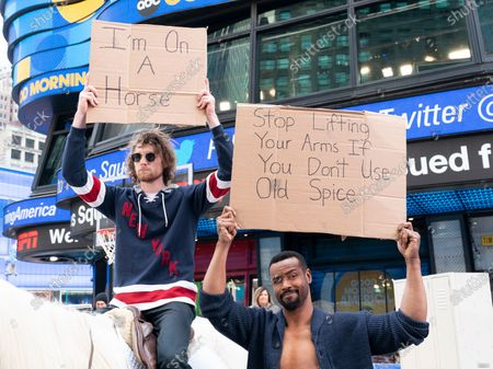 Actor Isaiah Mustafa and guest pose during Old Spice products promotion on Times Square