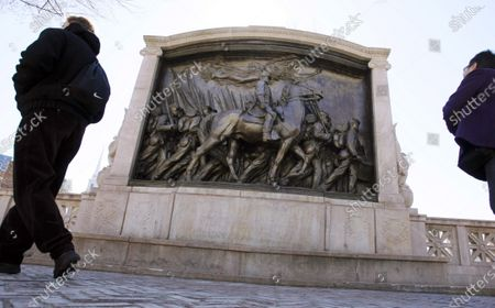 """People walk past the memorial to Union Col. Robert Gould Shaw and the 54th Massachusetts Volunteer Infantry Regiment, near the Statehouse in Boston. Amid the national reckoning on racism in July 2020, the memorial to the first Black regiment of the Union Army, the Civil War unit popularized in the movie """"Glory,"""" is facing scrutiny"""