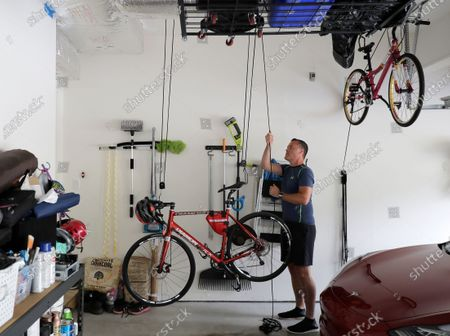 Neal Browning, the second person to receive a trial dose of a COVID-19 vaccine, lowers his bike in his garage before taking a ride, in Bothell, Wash. As the world's biggest COVID-19 vaccine study gets underway more than four months after Browning and 44 others became the first participants in a phase-one coronavirus vaccine study that has produced encouraging results, more than 150,000 Americans have filled out an online registry in recent weeks signaling interest to volunteer for other studies, according to a virologist with the Fred Hutchinson Cancer Research Institute in Seattle