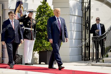 """President Donald Trump, center, and Veterans Affairs Secretary Robert Wilkie, left, arrive to greet Terry Sharpe, known as the """"Walking Marine"""" at the White House in Washington, . Sharpe has walked from Summerfield, N.C., to Washington to raise awareness of the current veteran suicide rate"""