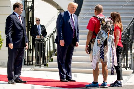 """President Donald Trump, accompanied by Veterans Affairs Secretary Robert Wilkie, left, and Karen Pence, the wife of Vice President Mike Pence, right, greets Terry Sharpe, known as the """"Walking Marine"""" at the White House in Washington, . Sharpe has walked from Summerfield, N.C., to Washington, to raise awareness of the current veteran suicide rate"""