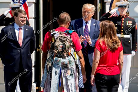 """President Donald Trump, accompanied by Veterans Affairs Secretary Robert Wilkie, left, and Karen Pence, the wife of Vice President Mike Pence, right, greets Terry Sharpe, center, known as the """"Walking Marine"""" at the White House in Washington, . Sharpe has walked from Summerfield, N.C., to Washington to raise awareness of the current veteran suicide rate"""