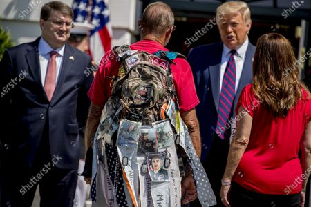 """Photographs of soldiers are clipped to the backpack of Terry Sharpe, center, known as the """"Walking Marine"""" as he is greeted by President Donald Trump, second from right, Veterans Affairs Secretary Robert Wilkie, left, and Karen Pence, the wife of Vice President Mike Pence, right, at the White House in Washington, . Sharpe has walked from Summerfield, N.C., to Washington to raise awareness of the current veteran suicide rate"""