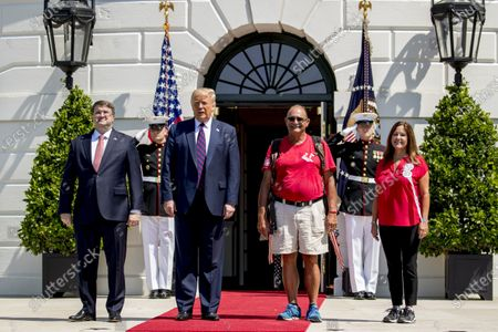 """President Donald Trump, Veterans Affairs Secretary Robert Wilkie, left, and Karen Pence, the wife of Vice President Mike Pence, right, pose for photographs with Terry Sharpe, third from right, known as the """"Walking Marine"""" as he arrives at the White House in Washington, . Sharpe has walked from Summerfield, N.C., to Washington to raise awareness of the current veteran suicide rate"""