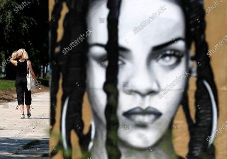 Woman walks past a mural depicting a singer Rihanna on a bank of Sava river in Belgrade, Serbia