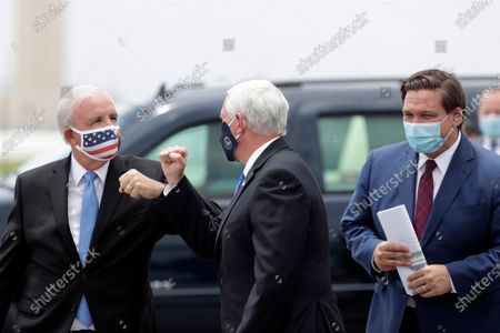 Vice President Mike Pence, center, elbow bumps Miami-Dade County Mayor Carlos Gimenez as Florida Gov. Ron DeSantis looks on at Miami International Airport, in Miami. Pence was in Florida to mark the beginning of Phase III trials for a Coronavirus vaccine