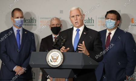 Vice President Mike Pence, second from left, speaks during a news conference as Rep. Mario Diaz-Balart, R-Fla., left, Food and Drug Administration Commissioner Dr. Stephen Hahn, second from left, and Florida Gov. Ron DeSantis, right, look on at the University of Miami Miller School of Medicine Don Soffer Clinical Research Center, in Miami. Pence was in Florida to mark the beginning of Phase III trials for a coronavirus vaccine
