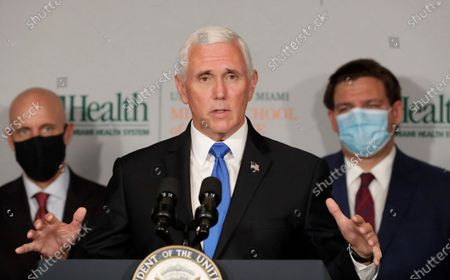 Vice President Mike Pence, center, gestures as he speaks during a news conference with Food and Drug Administration Commissioner Dr. Stephen Hahn, left, and Florida Gov. Ron DeSantis, right, at the University of Miami Miller School of Medicine Don Soffer Clinical Research Center, in Miami. Pence was in Florida to mark the beginning of Phase III trials for a coronavirus vaccine