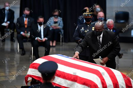 John-Miles Lewis touches the flag-draped casket of his father, Rep. John Lewis, D-Ga.,, in the Rotunda of the U.S. Capitol in Washington