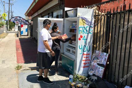 Volunteers Bryant Rodriguez and his daughter Vanessa Rodriguez stock a refrigerator with free food for people in need in Los Angeles on . A network called, LA Community Fridge, has placed a number of them across the Los Angeles area, from the Highland Park neighborhood north of downtown to Exposition Park near the University of Southern California to the seaside city of Long Beach, with plans to install more