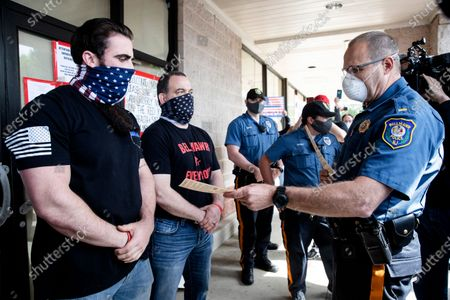 A police officer issues Atilis Gym co-owners Ian Smith, left, and Frank Trumbetti, center, summons outside their gym in Bellmawr, N.J., . After repeatedly defying the governor's order to remain closed during the COVID-19 pandemic Smith and Trumbetti have been arrested on contempt charges